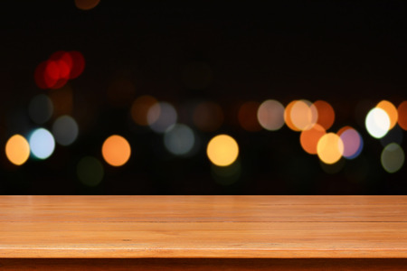 night table: Wood table top on colorful bokeh  background at night Stock Photo
