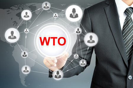 international organization: Businessman pointing on WTO (World Trade Organization) sign on virtual screen with people icons linked as network