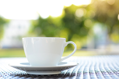 decaffeinated: Coffee cup on the table with blur green nature background