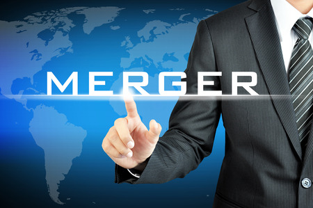 merge together: Businessman hand pointing to MERGER sign on virtual screen