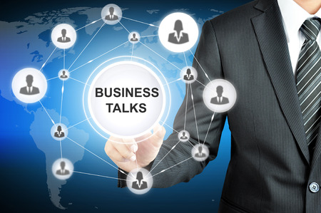 talks: Businessman pointing on BUSINESS TALKS sign on virtual screen with people icons linked as network Stock Photo