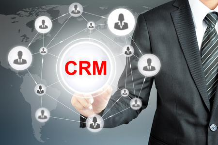 crm: Businessman pointing on CRM (Customer Relationship Management) sign on virtual screen with people icons linked as network