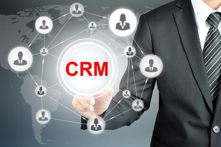 Geschäftsmann, der auf CRM (Customer Relationship Management) Zeichen auf virtuellen Bildschirm mit Menschen-Ikonen wie vernetzt