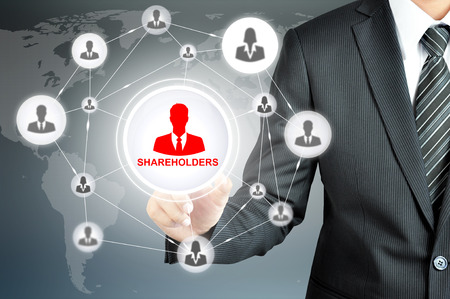 shareholders: Businessman pointing on SHAREHOLDERS sign on virtual screen with people icons linked as network