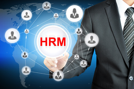 human resource management: Businessman pointing on HRM (Human Resource Management ) sign on virtual screen with people icons linked as network Stock Photo