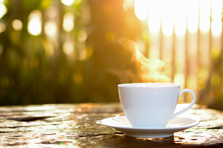 Hot coffee in the cup on old wood table with sunlight & blur green nature background