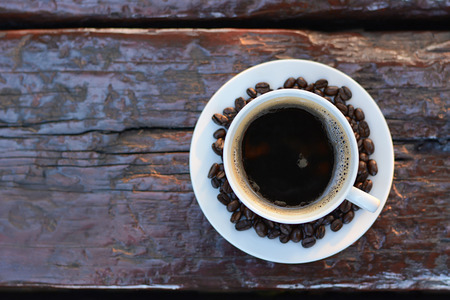 decaffeinated: Black coffee in the cup on old wood table with coffee beans - top view with copy space