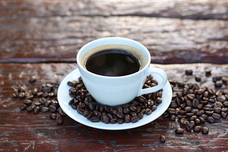 decaffeinated: Black coffee in the cup on old wood table with coffee beans