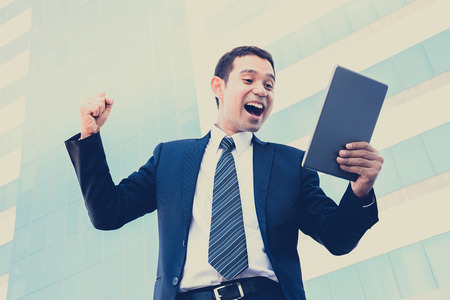 enthusiastic: Businessman yelling & raising his fist while looking at tablet pc - vintage & retro style color effect