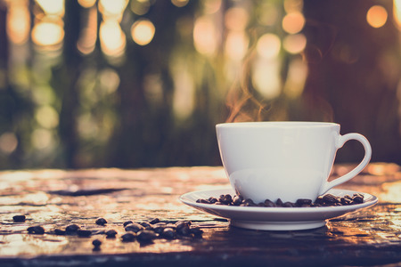 decaffeinated: Hot coffee in the cup on old wood table with blur dark green nature background - vintage style