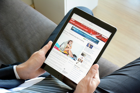 news online: Businessman using tablet, reading BBC news online on BBC website