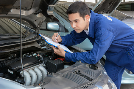 automotive repair: Auto mechanic (or technician) checking car engine at the garage
