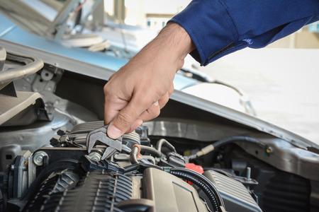 mecanica industrial: La mano del mecánico con la fijación de la llave del motor del coche Foto de archivo