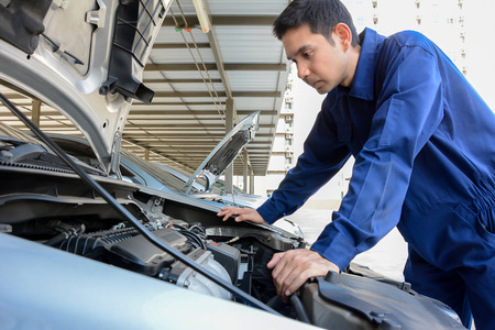 Auto mechanic (or technician) checking car engine
