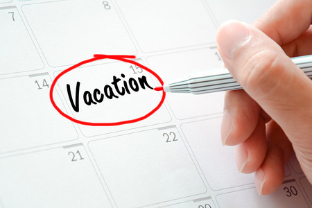 jot: Vacation text on the calendar (or desk planner) circled with red marker Stock Photo