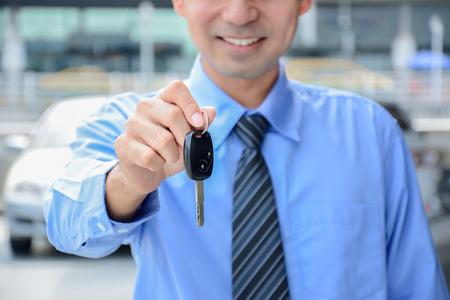 Businessman giving a car key - car sale, rental & insurance concepts photo