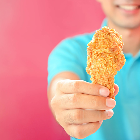 A man giving fried chicken leg or drumstick photo