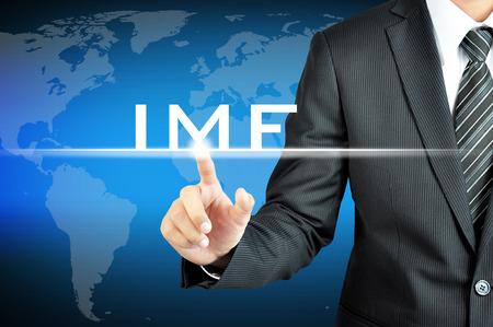 monetary: Businessman hand pointing to IMF (International Monetary Fund) sign on virtual sceen