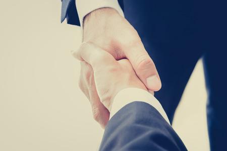 Apretón de manos de hombres de negocios en la vendimia efecto de color (retro) - éxito, felicitaciones, saludo y conceptos asociados de negocios