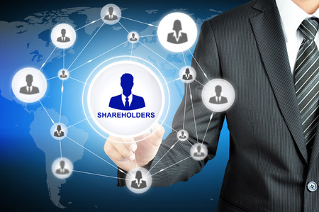 Businessman pointing on SHAREHOLDERS sign on virtual screen with people icons linked as network