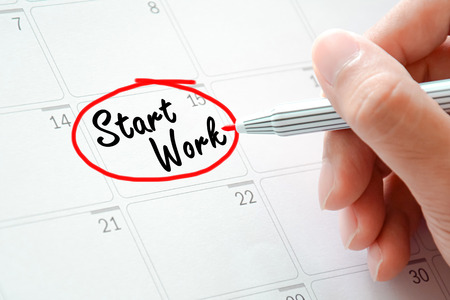 jot: Start Work texts on the calendar (or desk planner) circled with red marker Stock Photo