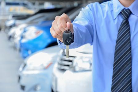 automobile sales: Businessman giving a car key - car sale, rental & insurance concepts