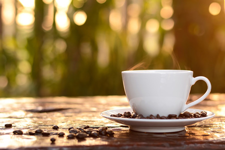 decaffeinated: Hot coffee in the cup on old wood table with blur dark green nature background - soft focus Stock Photo
