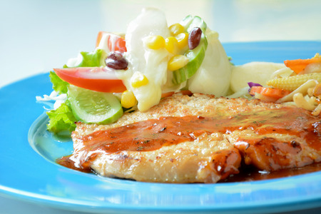 Pan fried pork steak with mix vegetable salad on colorful blue plate photo