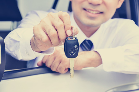 sell: Smiling man giving car key while sitting in the car, car insurance, sale & rental concepts - vintage (retro) style color effect Stock Photo