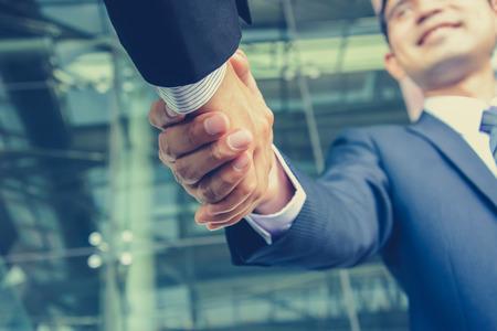 company merger: Handshake of businessmen in vintage (retro) color effect - success, congratulation, greeting & business partner concepts