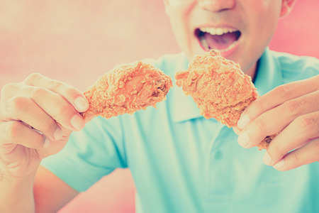 A man with opening mouth about to eat deep fried chicken legs or drumsticks -vintage (retro) style color effect photo
