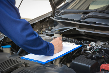 vehicle part: Auto mechanic (or technician) checking car engine at the garage