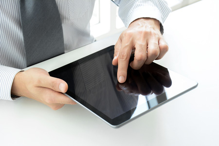 man using computer: Businessman using tablet pc on the table with one hand touching the screen