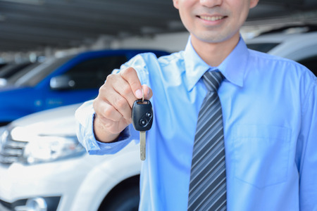 transportation company: Businessman giving a car key - car sale, rental & insurance concepts