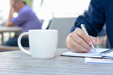 jot: A man hand writing on notebook with coffee cup beside Stock Photo