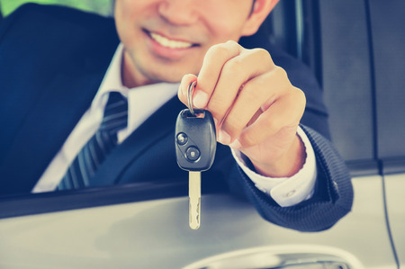 Businessman giving a car key - vintage style color effect photo