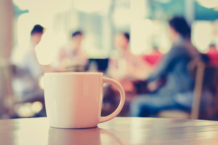Coffee cup on the table with people in coffee shop as blur background - vintage (retro) style color effect Imagens