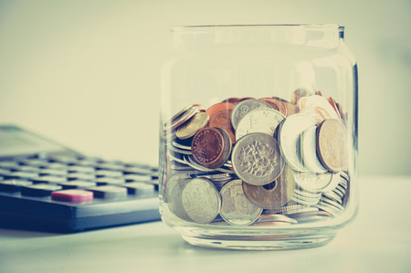 frugal: Coins in the glass jar, mixed Asian multi currencies - vintage (retro) color effect