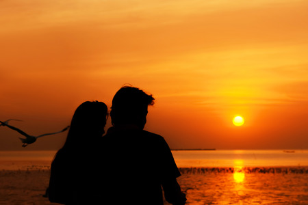 male and female: Silhouette of male & female as couple at the seacoast in romantic twilight sunset background