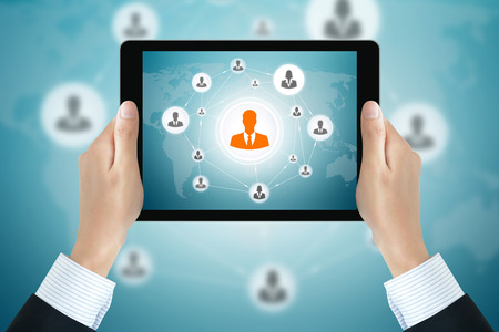 online: Businessman hands holding tablet pc with businesspeople icons linked as network on the screen - online business & social network concepts Stock Photo