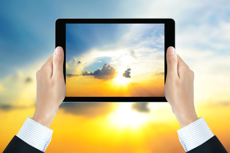 picture person: Businessman hands holding tablet pc, taking picture of the sun shining in the sky - bright business concept Stock Photo