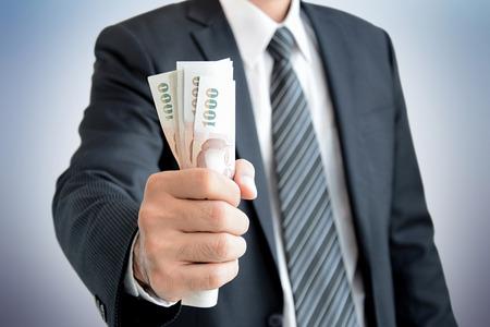 baht: Businessman hand grabbing money - Thai Baht (THB)