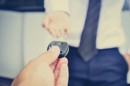 reach customers: Hand giving car key to a businessman, car sale & rental concepts - vintage (retro) style effect Stock Photo