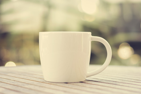 decaffeinated: Coffee cup on wood table with blur background - vintage (retro) style color effect Stock Photo