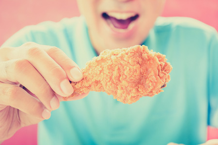 A man with opening mouth about to eat deep fried chicken leg or drumstick - vintage style color effect photo