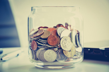 accumulate: Coins in the glass jar, mixed Asian multi currencies - vintage (retro) color effect