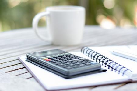 calculadora: Calculadora y lápiz sobre módulo de copia en la mesa de madera con fondo de la taza de café borrosa - estilo de enfoque suave