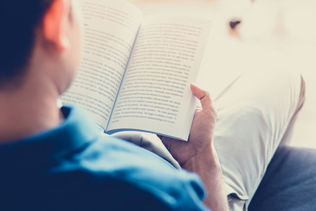Man reading book while sitting on the couch - soft focus with vintage color effect Stock Photo