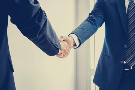 saludo de manos: Apret�n de manos de hombres de negocios; �xito, Negociaci�n y socios de negocios conceptos - efecto de color de la vendimia con enfoque suave Foto de archivo