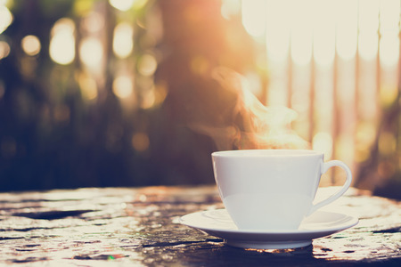 Hot coffee on old wood table with blur background of sunlight shining through the trees - soft focus, vintage style color effect Archivio Fotografico